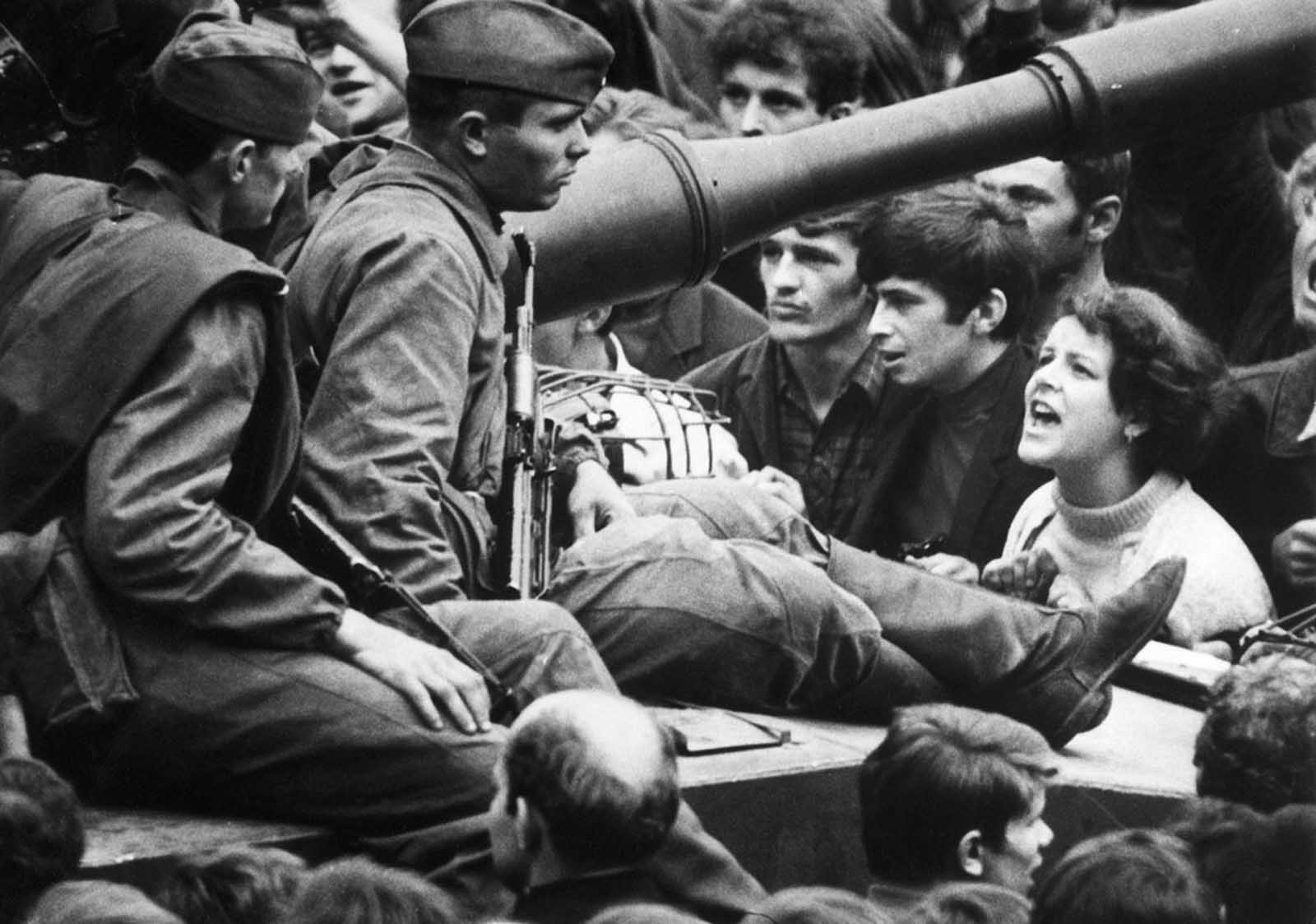 A young Czech lets her feelings be known as she shouts at Soviet soldiers sitting on tanks in the streets of Prague on August 26, 1968.
