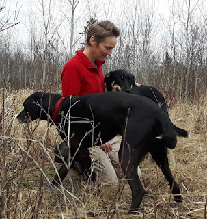 Writer and dog trainer Kristi Benson in a field with two dogs