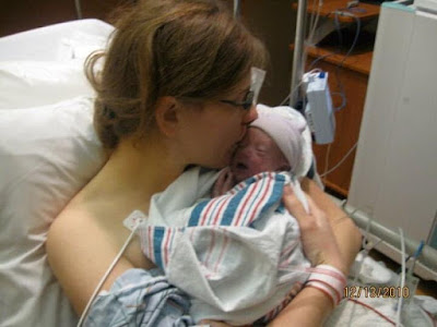 Woman holding child after traumatic birth experience. Woman is in hospital bed, kissing child, with hospital monitors in the background.