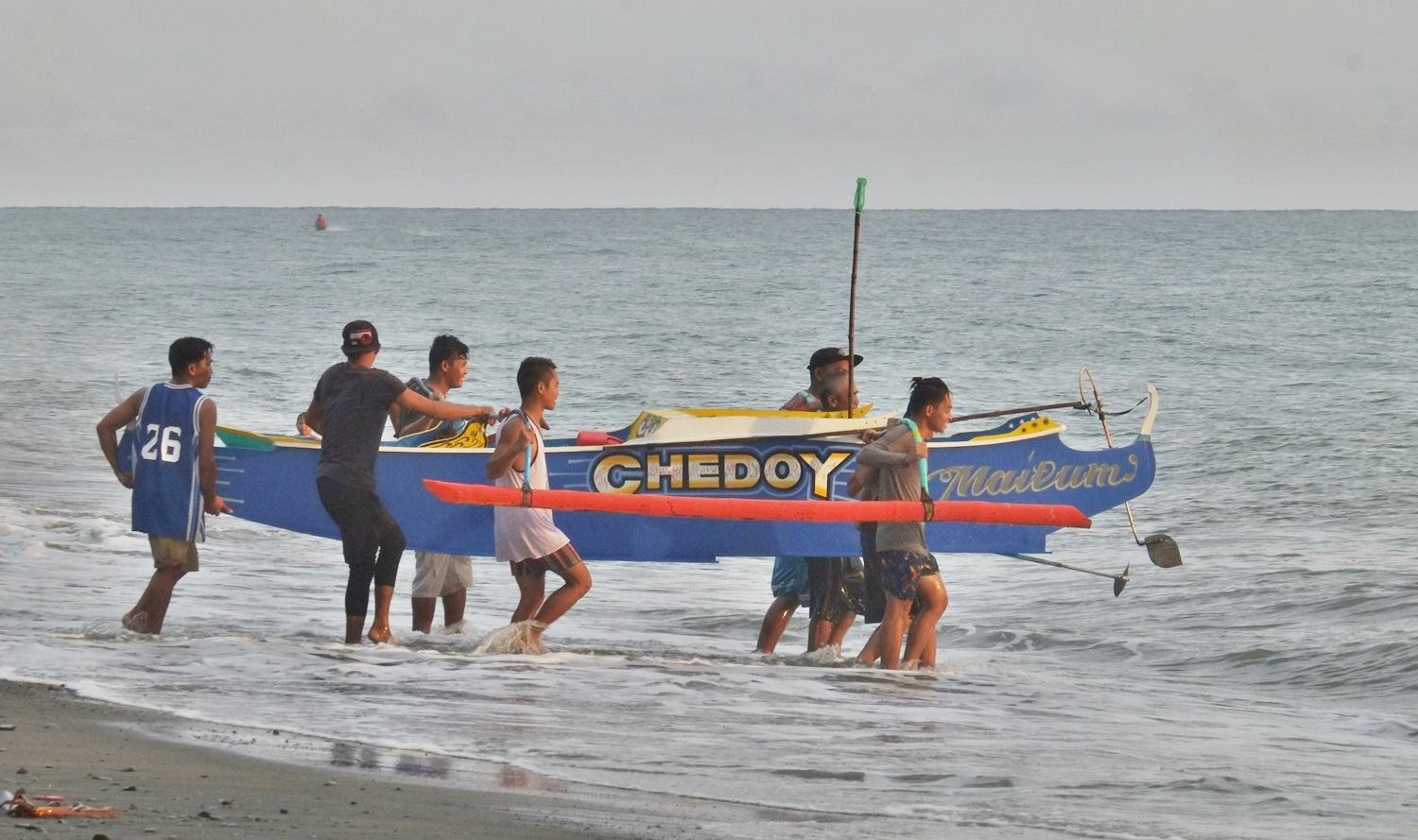 Fishermen helping each other in carrying a small fishing boat