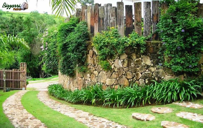 Caminhos de pedra moledo ao lado do muro de pedra com a execução do paisagismo.