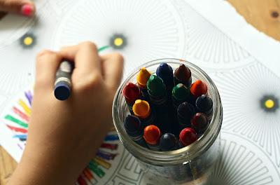 صورة ليد طفل صغير يرسلم ويلون وبجانبه مجموعة ألوان من الشمع