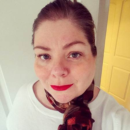 image of me from the shoulders up standing in a doorway wearing a white top and a multicolored scarf, with my hair pulled back and sporting bright red lips
