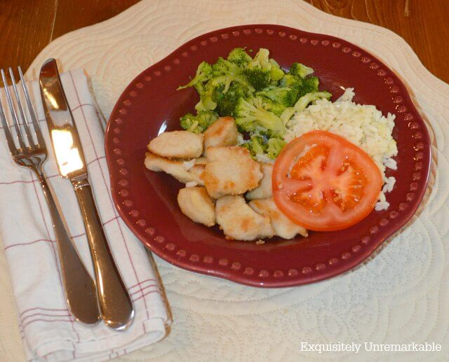 Chicken nuggets, rice, tomatoes and broccoli on red plate