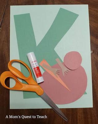 construction paper; letter k cut out of construction paper; glue stick; scissors