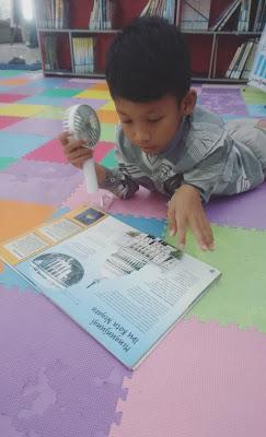 membaca buku di pojok dongeng perpustakaan bank indonesia saat parade dongeng surabaya 2019
