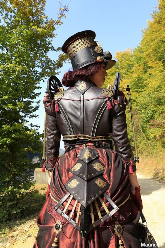 Woman dressed as in a steampunk train costume (wheels, traintracks, hat, goggles, corset, skirt)
