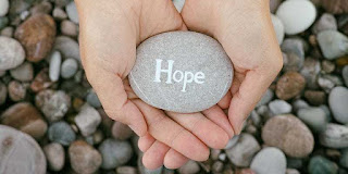 A person holding a pebble in their hands and on the pebble is written the word hope.