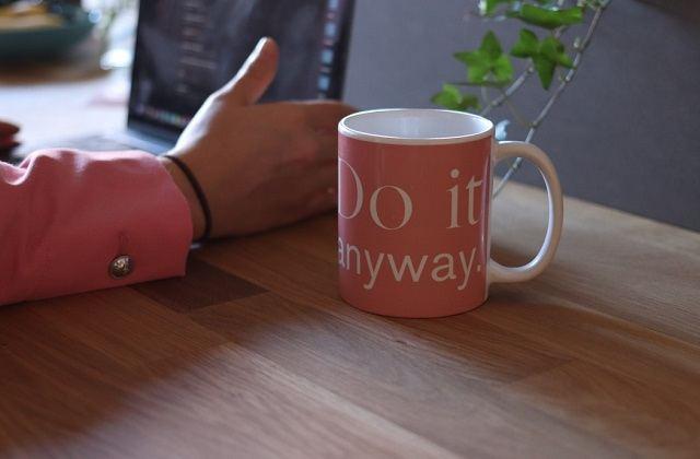 woman's hand on laptop pink mug on table