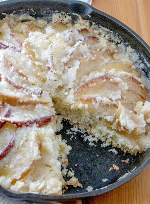 cast iron skillet full of dutch apple cake with buttery topping with one slice missing