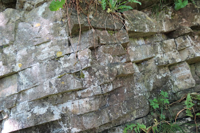 Layers of cracked strata in a rockface, looking almost like man-made bricks.