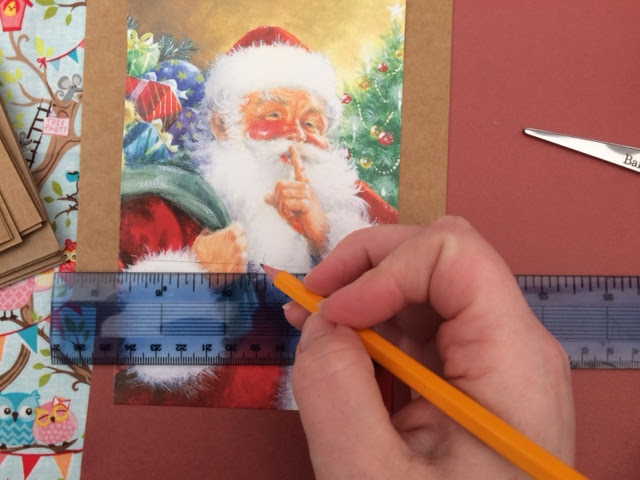 A Santa Christmas card being cut to size