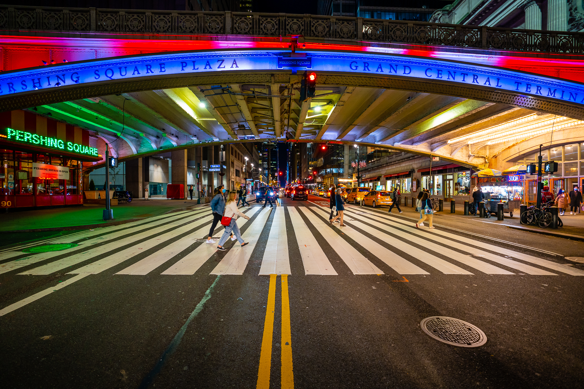 a wide angle photo of the bridge at pershing square new york grand central station