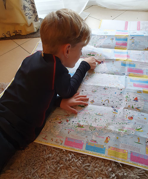 9 year old reading his map of adventures