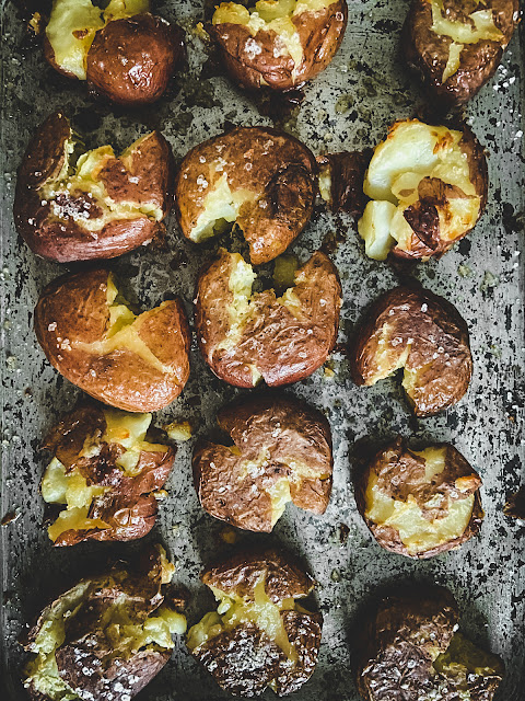 Ultra Crispy Smashed Potatoes, sweet little potatoes crispy on the outside and creamy on the inside with a generous sprinkle of coarse salt.  There is nothing complicated or fussy about them–– just easy.