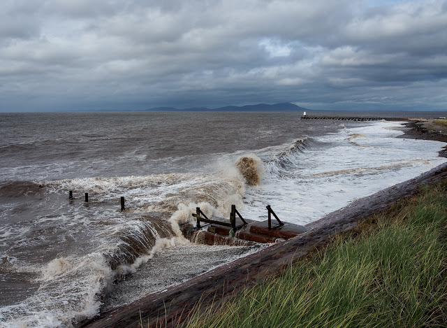 Photo of a large wave rolling in over the groyne on Maryport beach