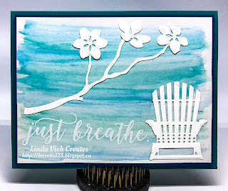 Linda Vich: June Wind Up and Projects. Watercolor pencils are used to create a wash as the backdrop for this Tropical card, complete with an Adirondack chair and branch with blossoms die cut with the Seasonal Layers Thinlits.