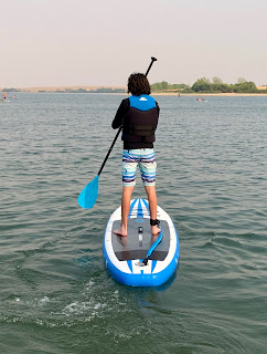 teen boy stands on a paddleboard in the water