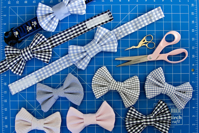 Homemade dog bow ties on a cutting mat with sewing supplies