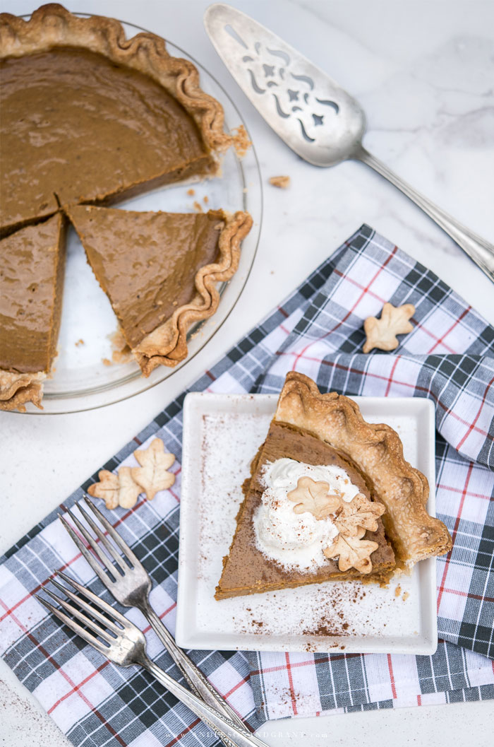 Pumpkin pie with one slice on a white plate