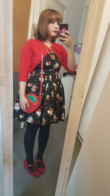 mirror selfie of auris in a black strawberry dress and a red strawberry bag