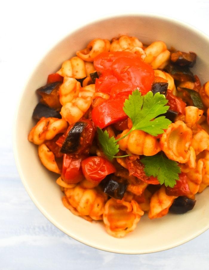 close up of pink pasta bowl full of ratatouille pasta