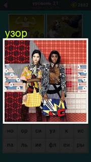 стоят две женщины около стены с узорами и одежда вся в узорах