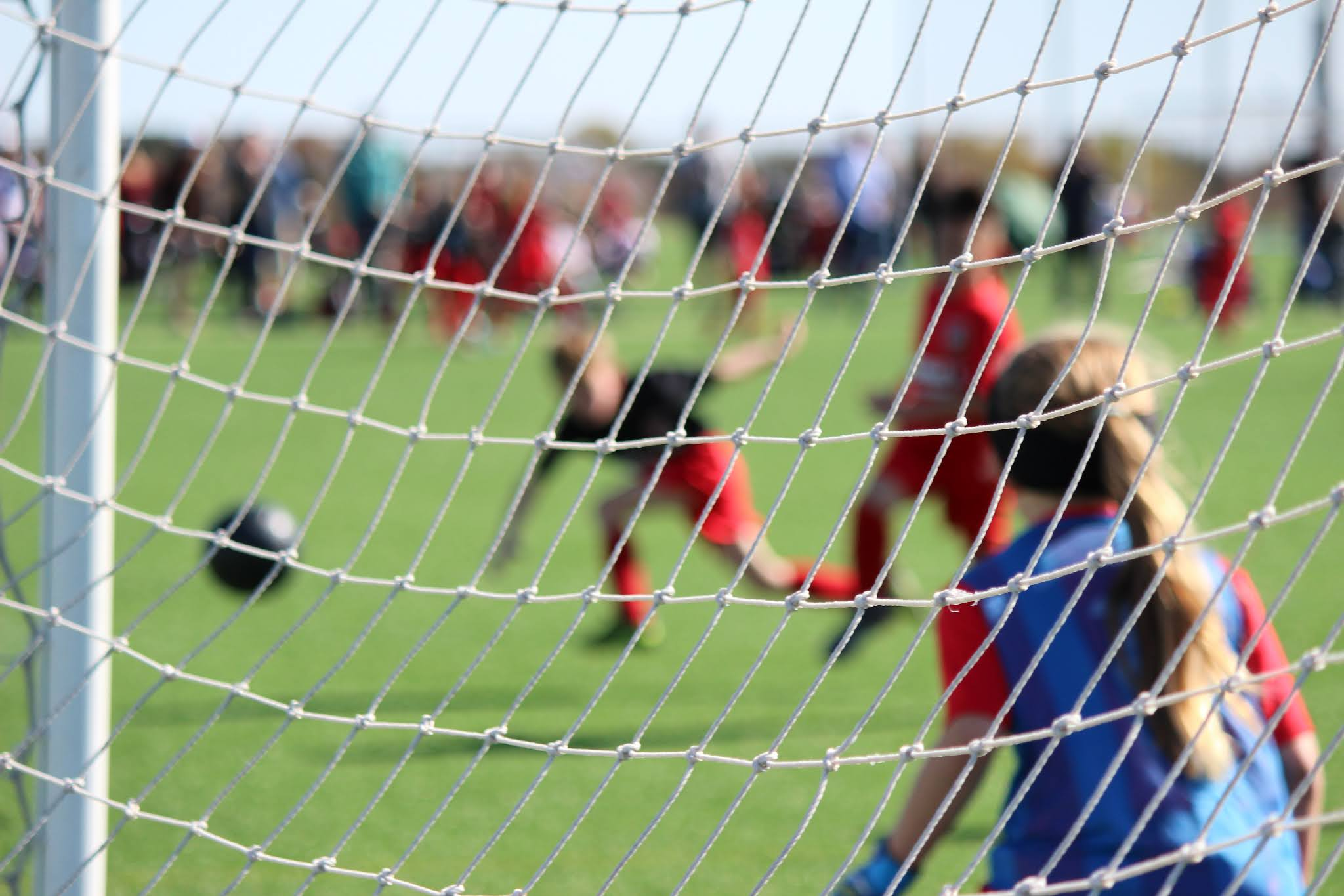 Free stock image by Alyssa Ledesma on Unsplash looking through a football goal at a football game played by children