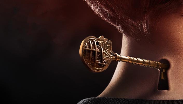 A nuca de um garoto de cabelo curto e tem uma chave entrando na nuca dele que tem um buraco que parece uma fechadura. A chave é dourada e na forma de uma cabeça.