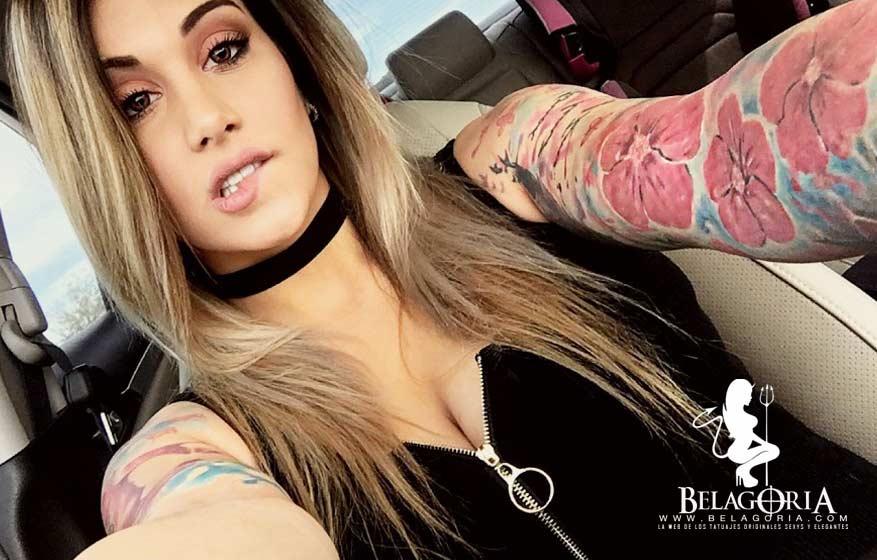 Se ve en la imagen a la actriz para adultos  Nikki Nichole en su coche, lleva en el brazo tatuajes de ibisco