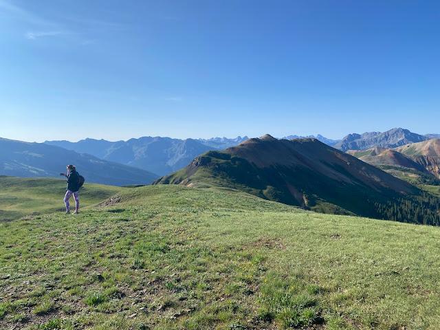 woman walking on a grassy mountain