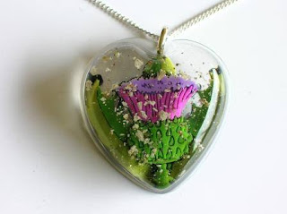 Heart shaped pendant with ashes and a Thistle