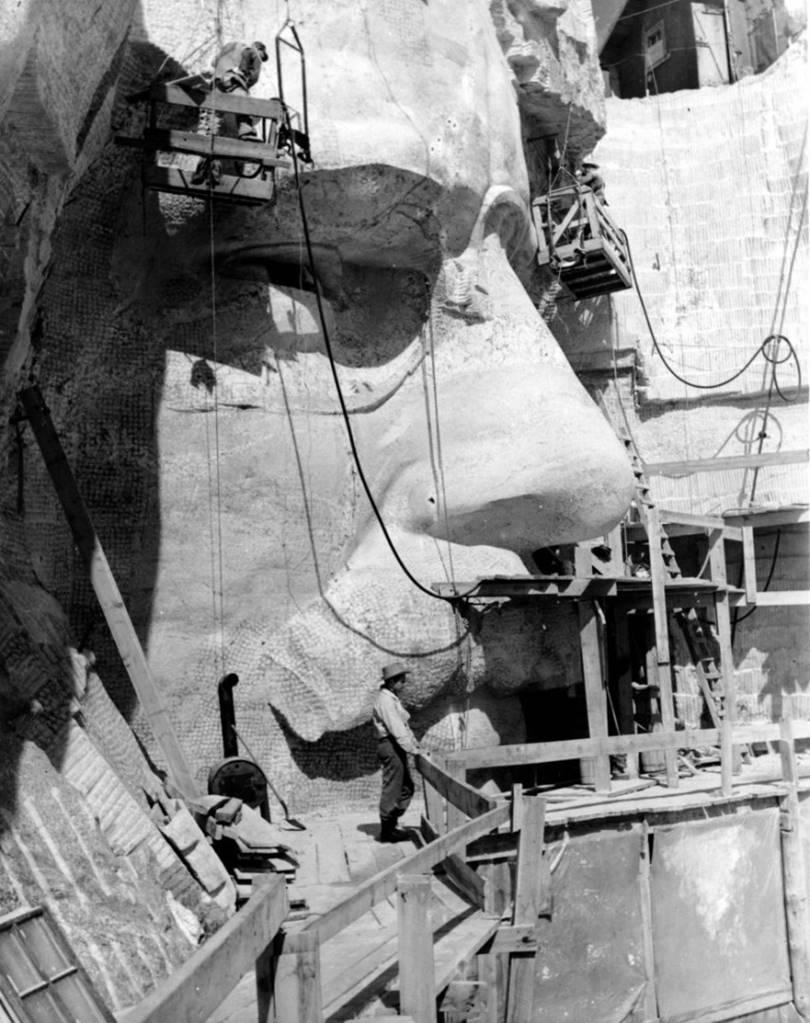 Sculptor Lincoln Borglum (son of Gutzon Borglum) on scaffolding near the face of the sculpture of President Theodore Roosevelt.