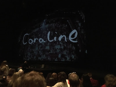 photo shows curtain reading 'Coraline' and projected image of the auditorium and audience