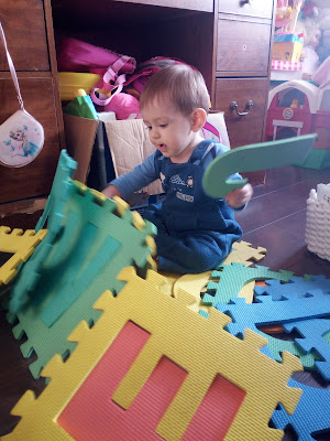 Baby Milestones At 11 Months Old - Image Shows Baby Lifting Foam Mats From Floor