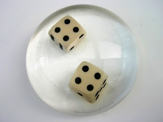 Dice encased within a paperweight