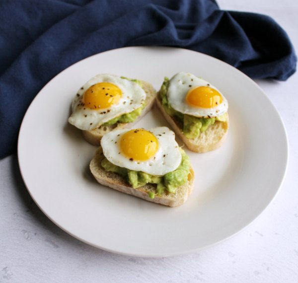 three avocado and quail egg crostini served on small plate