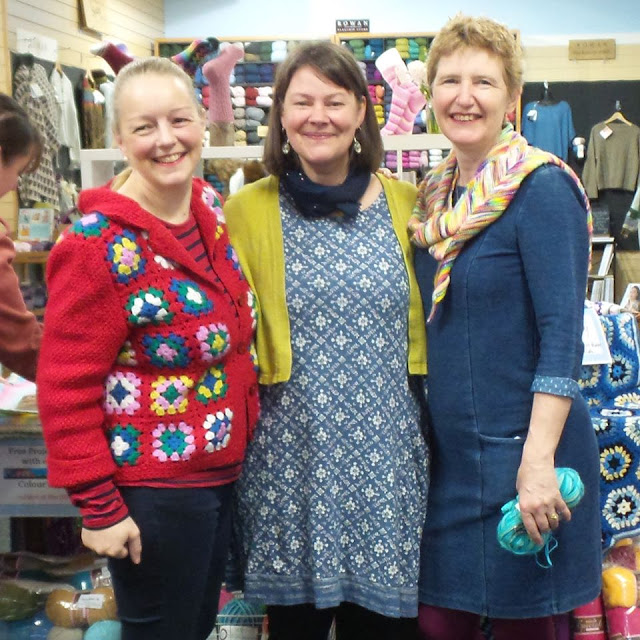 Image shows three women in a yarn shop.  Emma Varnam on the left wears a red crochet granny square cardigan and jeans, Lucy of Attic24 in the middle wears a blue and white tunic in a diamond pattern with a mustard cardigan and Christine Perry on the right wears a denim dress and a multi-coloured scarf