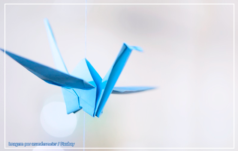 a imagem mostra um pequeno tsuru azul (pássaro de origami) pendurado em uma linha, sobre um fundo branco
