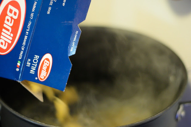 Pasta being poured into a pot of boiling water.