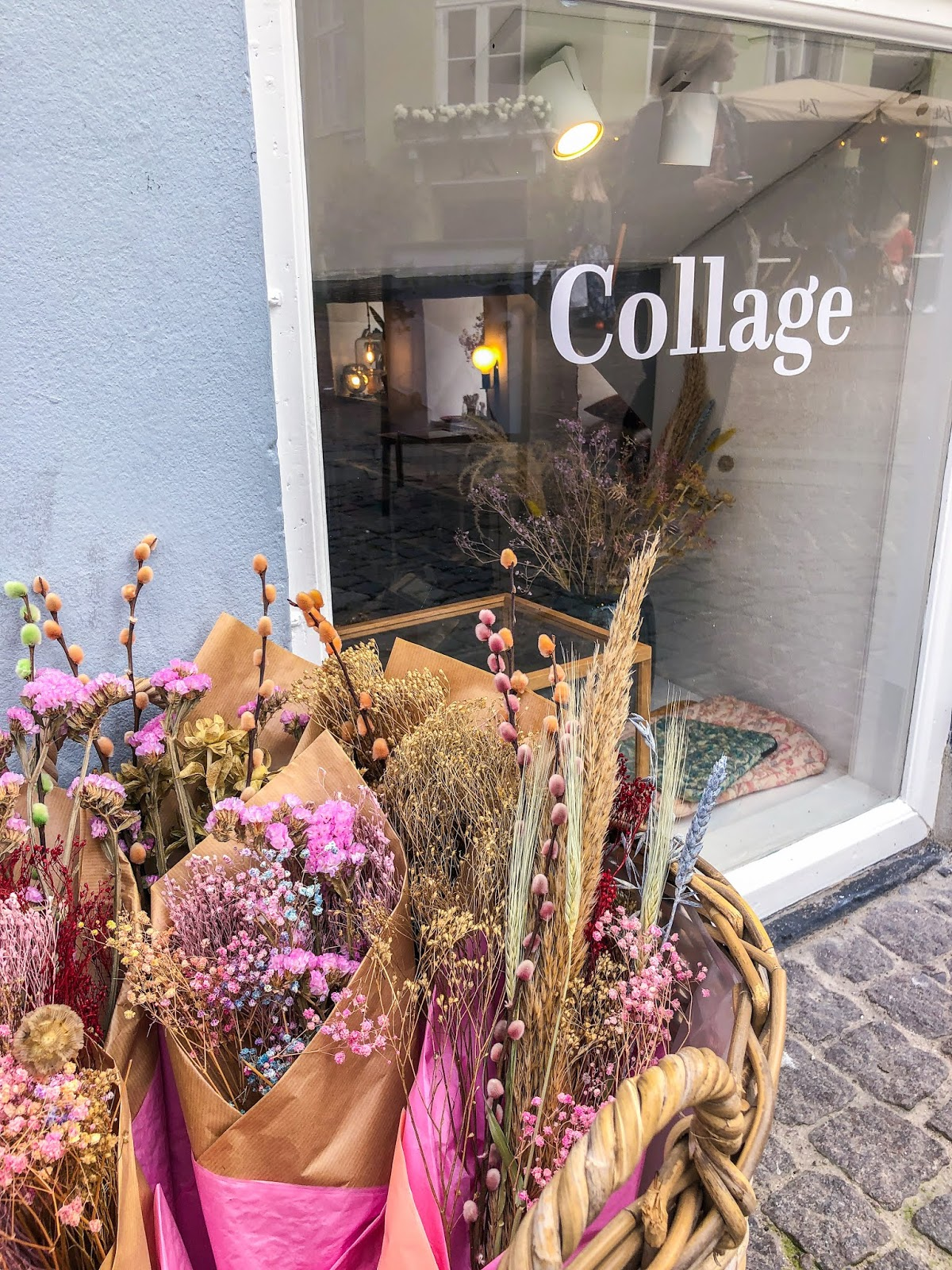 bounces of pastel pink flowers outside shop window of 'Collage' in Copenhagen