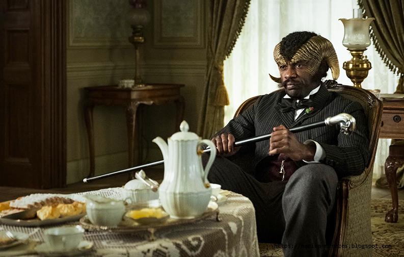 A imagem mostra um homem negro sentado à cabeceira da mesa. Ele possui chifres que dão uma volta, como chifres de um bode, e segura uma bengala. Veste um terno cinza e calças pretas, à sua volta, móveis e outros objetos de decoração clássicos, de madeira, no estilo vitoriano. A sua frente, uma mesa de café da manhã com pães e comidas do tipo