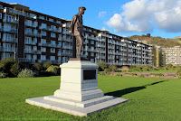 Commemorates Rolls' non-stop return flight across English Channel, 2nd June 1910. Co-founder Rolls Royce motor cars. Statue in front of seafront Gateway Flats facing English Channel. Matthew Webb bust is nearby. Skyline: Roman Pharos, St Mary-in-Castro church, Dover Castle.