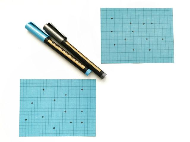 dwie niebieskie kartki w kratkę, na których zaznaczone są kropki i miejscach przecięć linii. Obok leża dwa markery w kolorze niebieskim i srebrnym