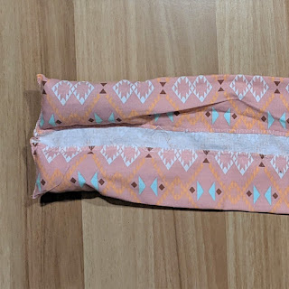 A rectangle of pink fabric with the long edges folded over and sewn down and the short edge sewn closed. The two tubes created have been stuffed, creating two cylinders connected by an inch of fabric.