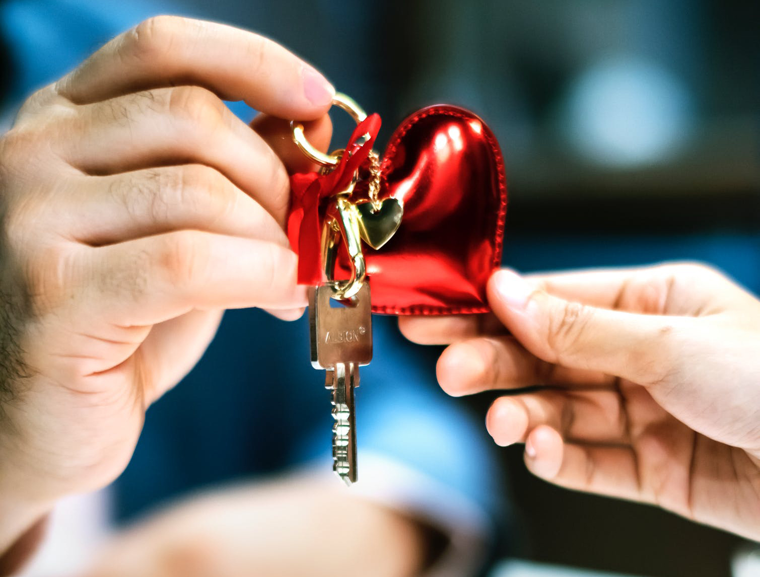 couple holding a love heart shaped keyring with a house key