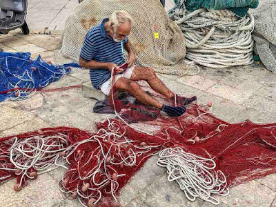 Fisherman works at his net in Gallipoli village of Apulia region, southern Italy