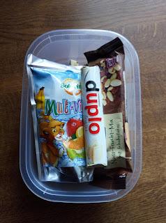 Naschbox mit Getränk und Knabberzeug: Duplo, Studentenfutter, Nüsse, Saft