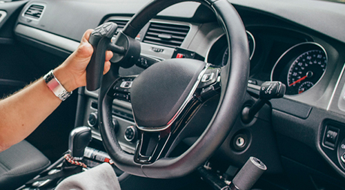 A hand gripping a steering wheel