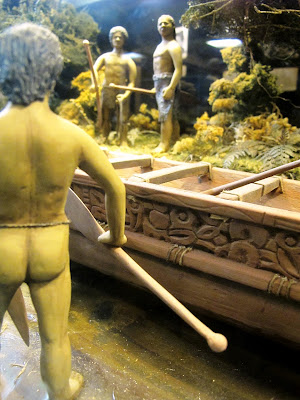One-twelfth-scale diorama of a maori waka (war canoe) at the edge of a river with people around it holding paddles.